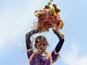 A female Govinda breaking Dahi Handi,