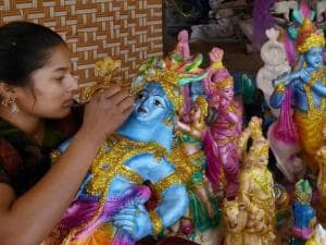 An artist gives final touches to an idol of Lord Krishna