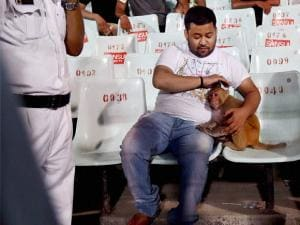 A monkey which appeared in the stand sits with people while a police man informs to the control room during IPL Match at Eden Garden in Kolkata.