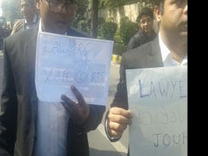 Journalists display placards at a protest march from Press Club of India to the Supreme Court