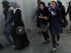Roshan mobile company employees leave the site of a suicide attack in Kabul