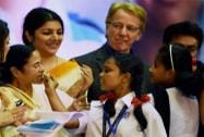 A student offering a piece of cake to West Bengal Chief Minister Mamata Banerjee