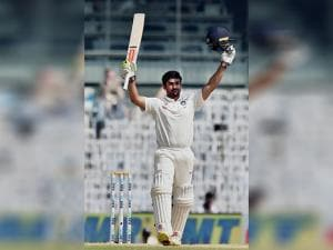 Karun Nair raises his bat after scoring his maiden century in an international match
