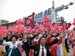 North Korean parade participants wave decorative bouquets of flowers and carry their country's national flag as they march with a model of the Unha space launch vehicle at the Kim Il Sung Square