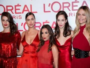 Actress Eva Longoria, center, poses with models, from left, Isabeli Fontana, Irina Shayk, Luma Grothe and Natasha Poly, for photographers upon arrival at the L'Oreal Red Obsession Party in Paris