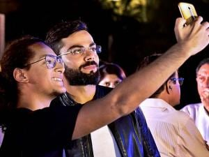 Virat Kohli poses for a selfie with a fan at the book launch of his biography, 'Driven'