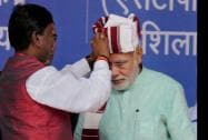 Prime Minister Narendra Modi is presented with a turban by BJP leader Arjun Munda