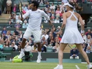 Martina Hingis of Switzerland with playing partner Leander Paes of India hit a return