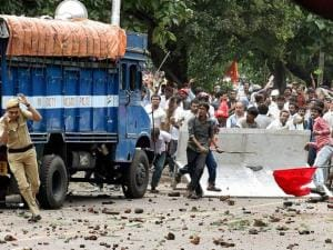 A police man tries to escape as activists of Left Front affiliated peasants organisation pelt stones