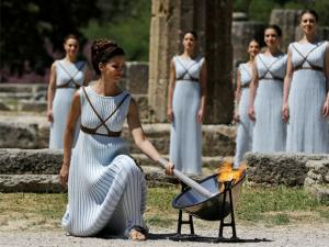 A dancer dressed as priestesses lights the Olympic flame with a parabolic mirror during the ceremonial lighting of the Olympic flame in Ancient Olympia, Greece