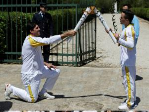 Former Brazilian volleyball player Giovane Gavio, left, receivesthe Olympic flame by Greek gymnast Eleftherios Petrounias, right, after the ceremonial lighting of the Olympic flame in Anci