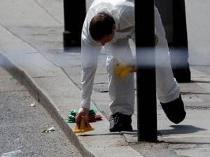 A forensic police officer places a marker on the pavement within a cordoned off area after an attack in the London Bridge area