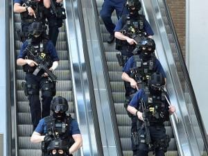 Armed police descend an escalator at the foot of the Shard outside London Bridge station