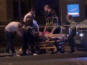 In this image made from PA Video footage, people receive medical attention in Thrale Street near London Bridge