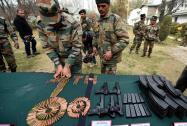 Army personnel display arms and ammunition recovered from poll-bound Kupwara district