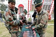 Army personnel display arms and ammunition recovered from poll-bound Kupwara District at Badami Bagh