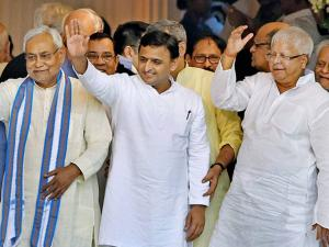 Bihar Chief Minister Nitish Kumar, Uttar Pradesh Chief Minister Akhilesh Yadav and RJD Chief Lalu Prasad Yadav wave hands to the people during the swearing- in ceremony
