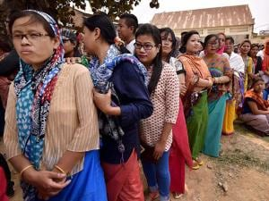Voters  stand in queues at a polling center to cast their votes
