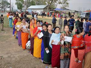 Voters  stand in queues at a polling center to cast their votes during the 1st phase of Manipur Assembly elections