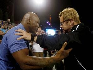 Sir Elton John greets Mike Tyson during a World Team Tennis exhibition