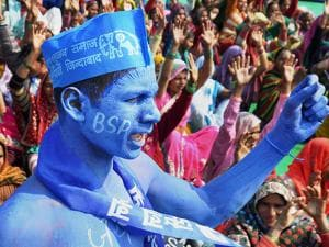 A BSP supporter paints himself in blue at an election rally of BSP