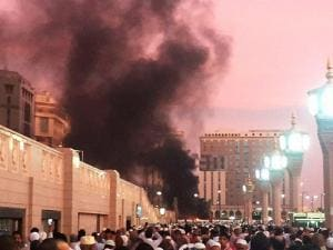 people stand by an explosion site in Medina
