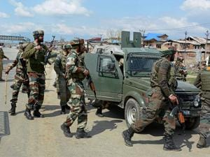 Army personnel conducting a search operation after one of their vehicles was targeted by militants