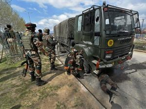 Soldiers keep vigil as an army jawan checks a military truck for damages which was targeted by militants near a hospital