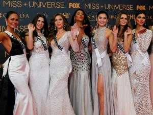 Miss Universe contestants blow kisses to photographers as they pose on the red carpet on the eve of their coronation