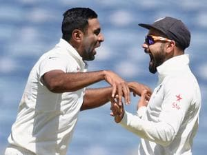 Indian bowler R Ashwin with captain Virat Kohli celebrates the wicket of Australian batsman Steve Smith during the first day of the first cricket test match in Pune