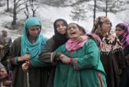 Women wailing over the deaths of their relatives  near the site of a landslide at village Laden in Chadoora in Budgam