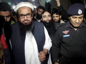 A Pakistani police officer escorts Hafiz Saeed  Chief of Pakistan's religious group Jamaat-ud-Dawa outside party's headquarters in Lahore