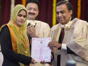 Chairman and MD of Reliance Industries Mukesh Ambani felicitating a student during the annual convocation of Mumbai University