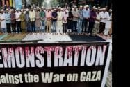 Muslims put up a banner against Israel's attack on Gaza while offering Friday prayers in front of Tipu Sultan Mosque in Kolkata