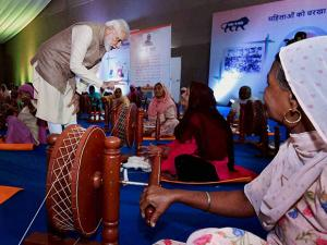 Narendra Modi interacts with the women after handing over charkhas