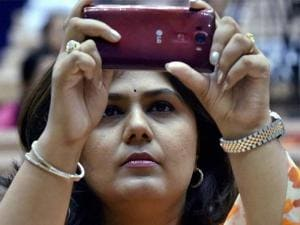 Maharashtra state minister Pankaja Munde uses mobile to take picture during the inaugural session of the National Conference of Women Legislators