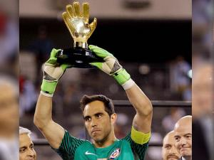 Chile goalkeeper Claudio Bravo holds up his trophy after the Copa America