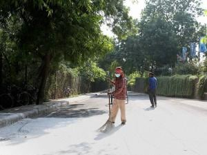 A worker cleans a road at National Zoological Park which was shut down temporarily amid bird flu scare in New Delhi