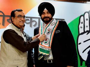 DPCC President Ajay Maken  presents the party scarf to Navjot Singh Sidhu as he is welcomed at a press conference