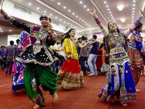 People in traditional dress plays dandia during the Navratri celebration in Bengaluru