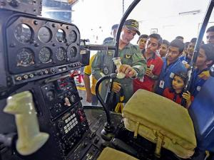 A Navy officer explains  school children about the helicopter during a air display as part of the Navy day celebration in Mumbai