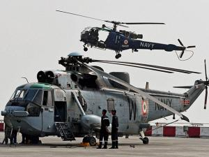 helicopters during an air display as part of the Navy day celebration in Mumbai