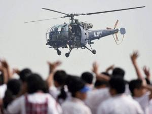 School children wave to a helicopter during an air display show as part of the Navy day celebration in Mumbai