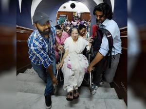 An elderly movie buff is carried on a wheelchair inside the hall of New Delhi's iconic theatre Regal Cinema