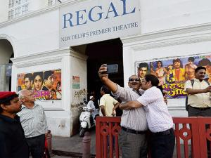 Movie buffs taking selfies in front of New Delhi's iconic theatre Regal Cinema