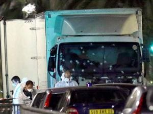 Forensic officers stands near a truck at Nice City