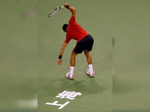 Novak Djokovic of Serbia smashes his racquet in frustration