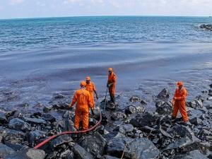Members of the Pollution Response Team removing black oil washed ashore as a thick oily tide from the sea lapped at the coast