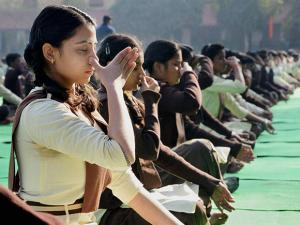 School children perform Yoga during a programme on the birth anniversary of Swami  Vivekananda in Jabalpur