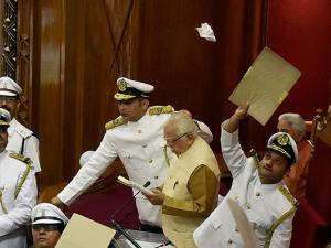 Marshals protecting UP Governor Ram Naik from paper balls thrown by agitating SP MLAs